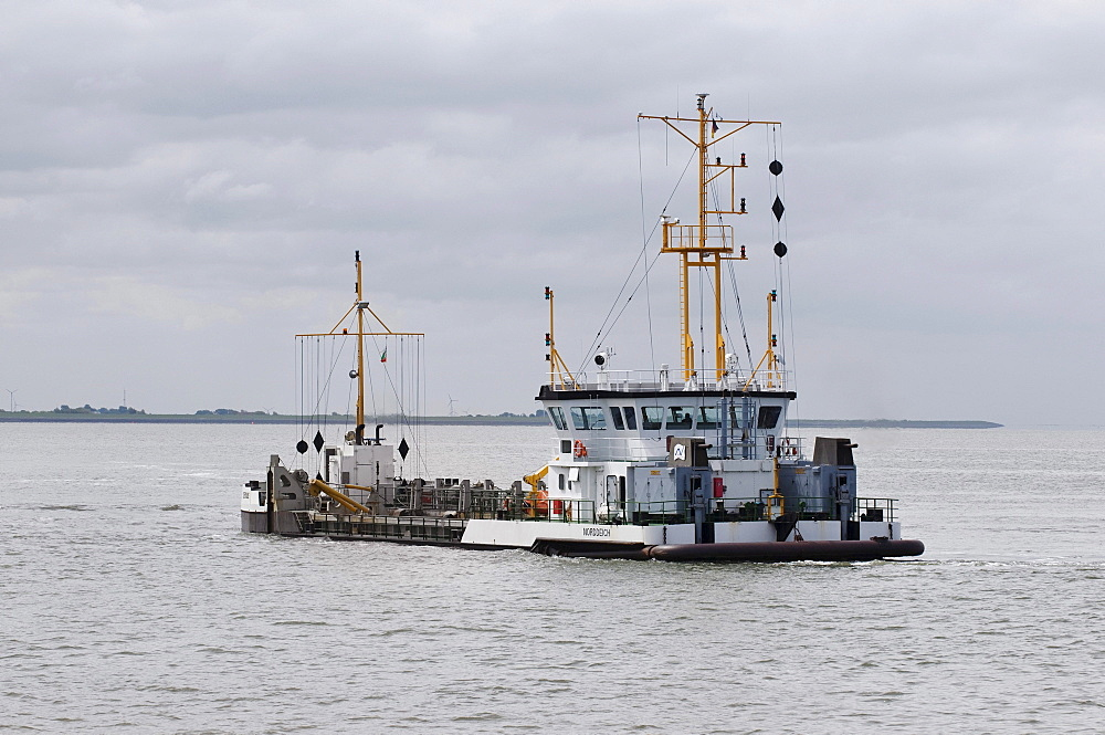Ship for the removal of silt and sand from the harbour bed, in front of Norddeich in the Wadden Sea, Lower Saxony, Germany, Europe