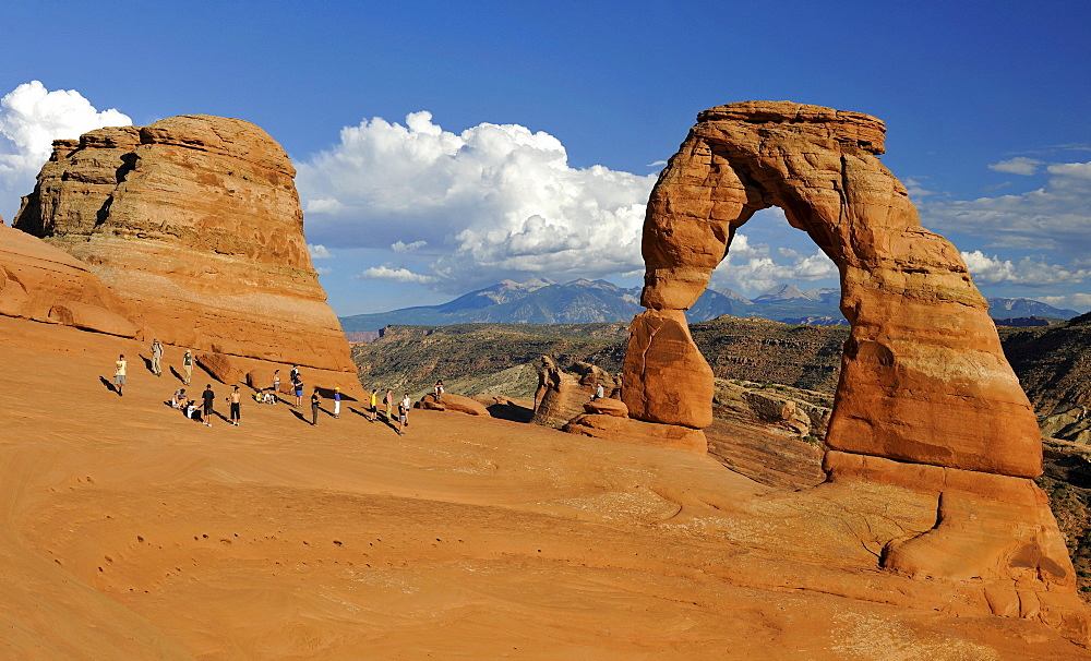 Tourists taking pictures in front of Delicate Arch, rock arch, La Sal Mountains, Arches National Park, Moab, Utah, Southwestern United States, United States of America, USA