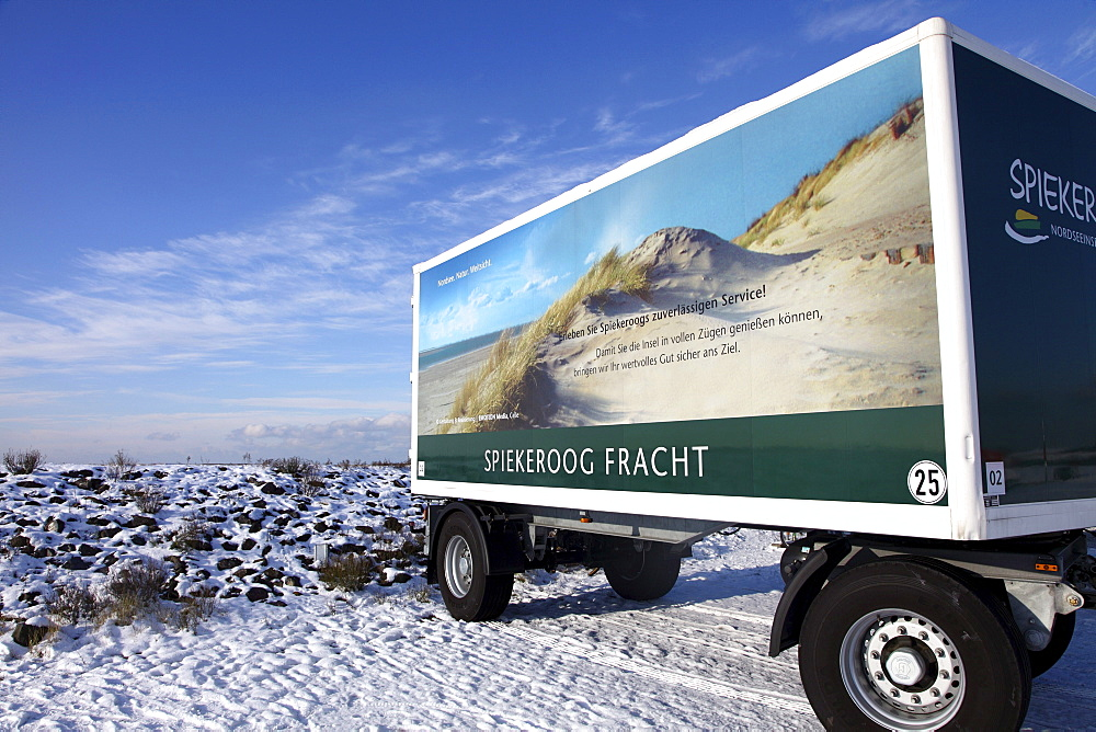 Cargo trailer with a summer and beach scene on it at the port of Spiekeroog, in winter, Spiekeroog island, one of the East Frisian Islands in the North Sea, Lower Saxony, Germany, Europe
