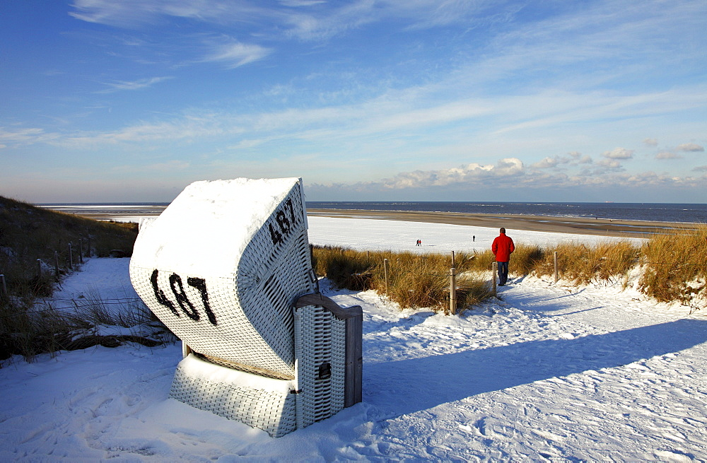 Winter, snow-covered beach with a roofed wicker beach chair, East Frisian North Sea island of Spiekeroog, Lower Saxony, Germany, Europe