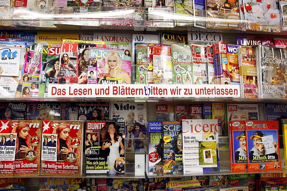 """Shelves with magazines in a shop, lettering """"Das Lesen und Blaettern bitten wir zu unterlassen"""", German for """"Please refrain from reading or skimming through the magazines"""""""