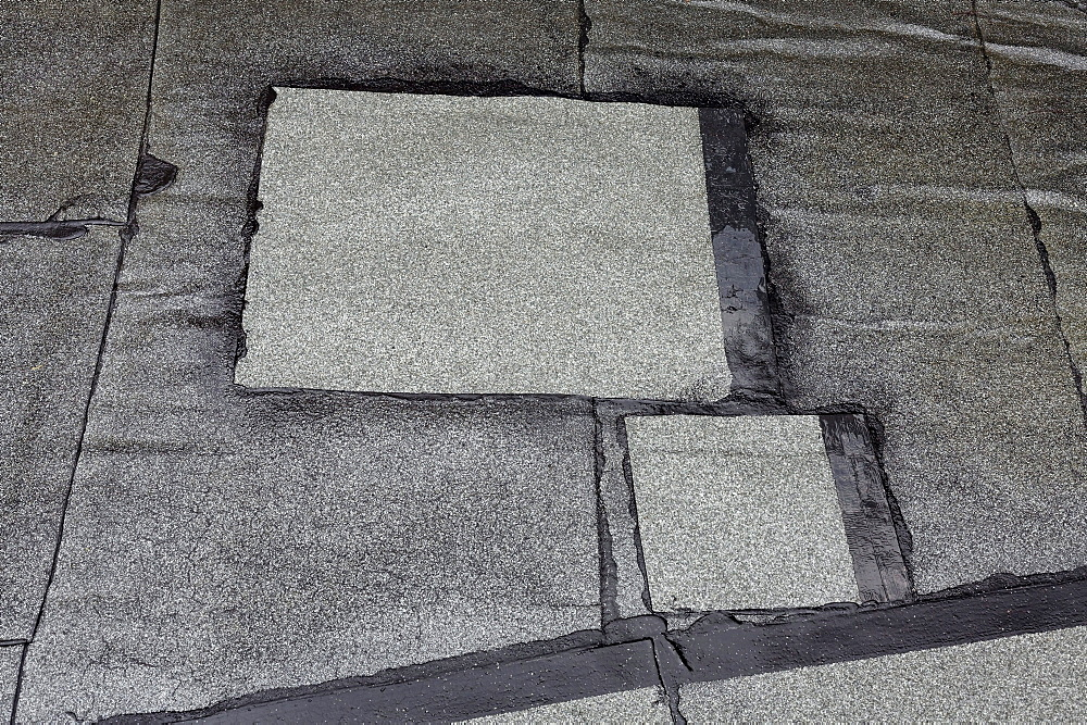 Patched-up, repaired areas on a roof made of roofing felt