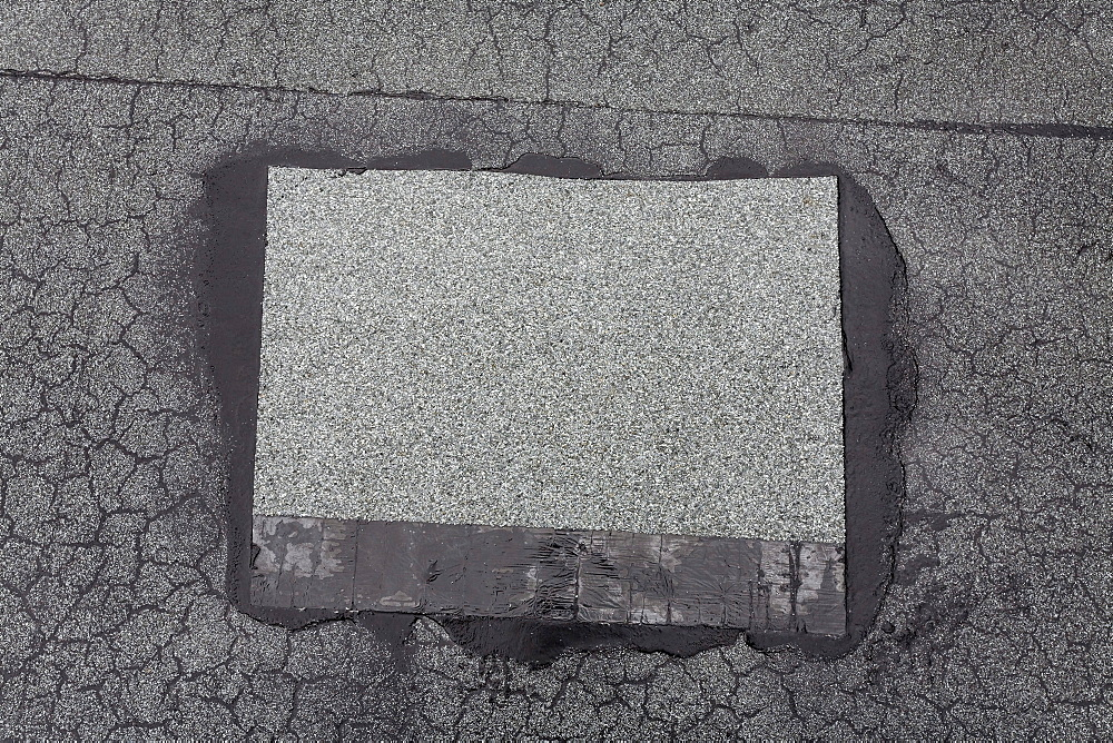 Patched-up, repaired area on a roof made of roofing felt