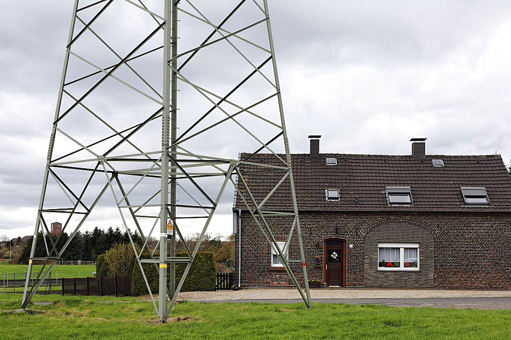 Small farmhouse located close to an electricity pylon, Gellep-Stratum district, Krefeld, Lower Rhine region, North Rhine-Westphalia, Germany, Europe