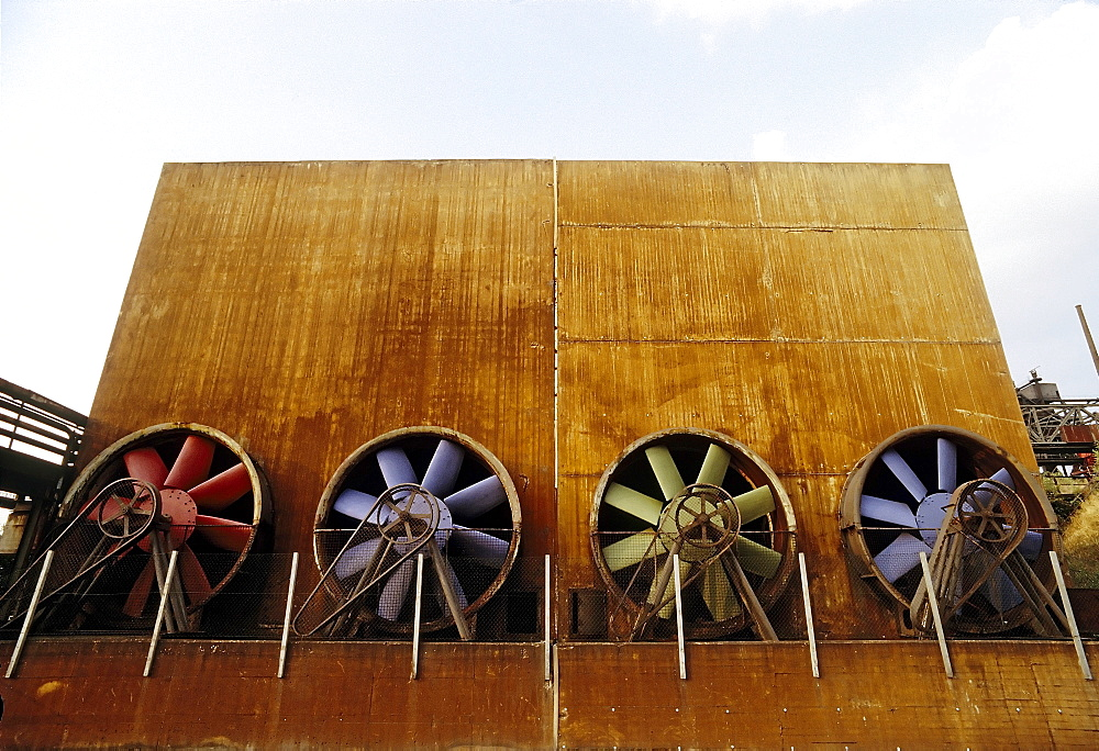 Industrial building with four brightly painted ventilation propellers, former Thyssen blast furnace plant, today Duisburg-Nord Landscape Park, North Rhine-Westphalia, Germany, Europe