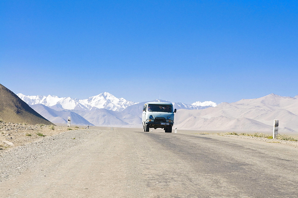 Country road leading to snow covered mountains, Karakul, Pamir Mountains, Tajikistan, Central Asia