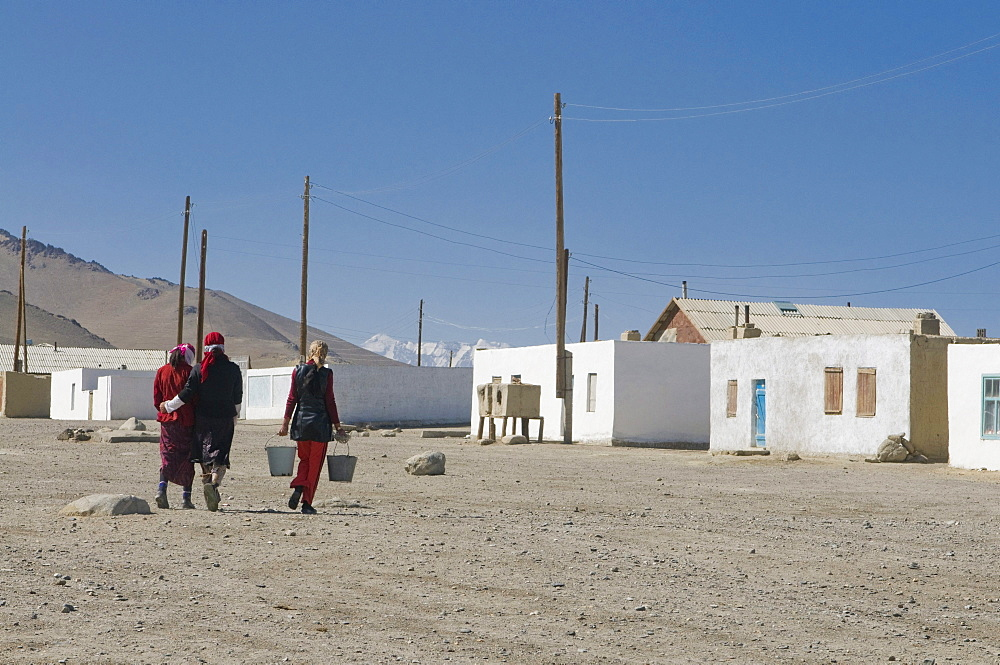 Women coming from a well, water reservoir in a village, Karakul, Tajikistan, Central Asia