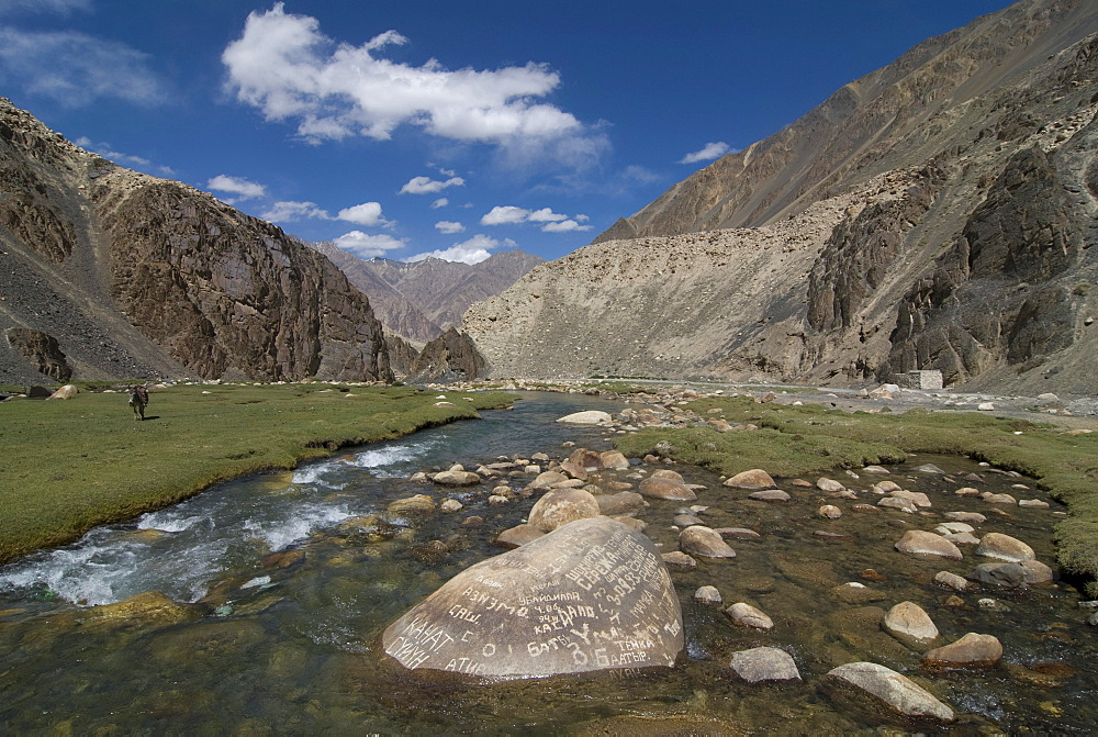 Inscriptions on a rock in the river flowing through Madyian Valley, Pamir Mountains, Tajikistan, Central Asia