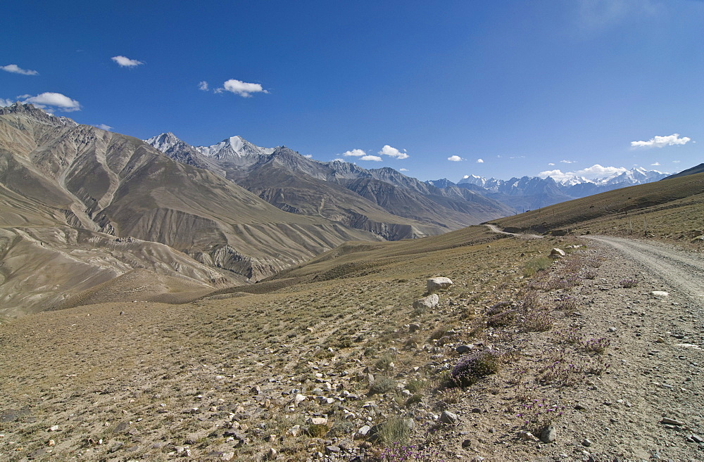 Dirt road leading through mountainous landscape, Wakhan Valley, Pamir Mountains, Tajikistan, Central Asia