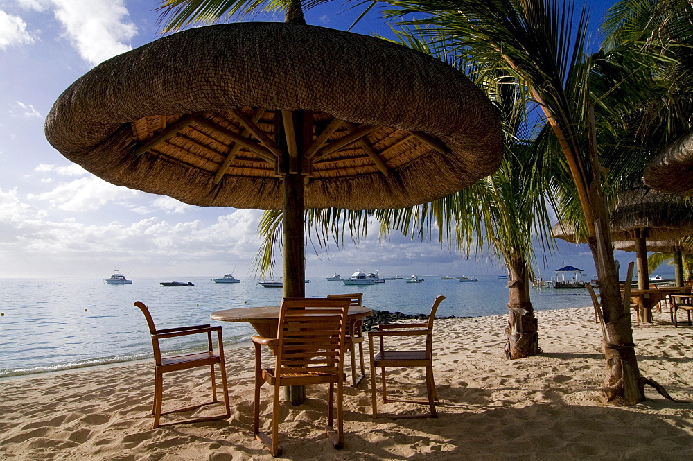 Table and chairs under sunshade on the beach of Le Paradis Hotel, Mauritius, Africa - 832-126308