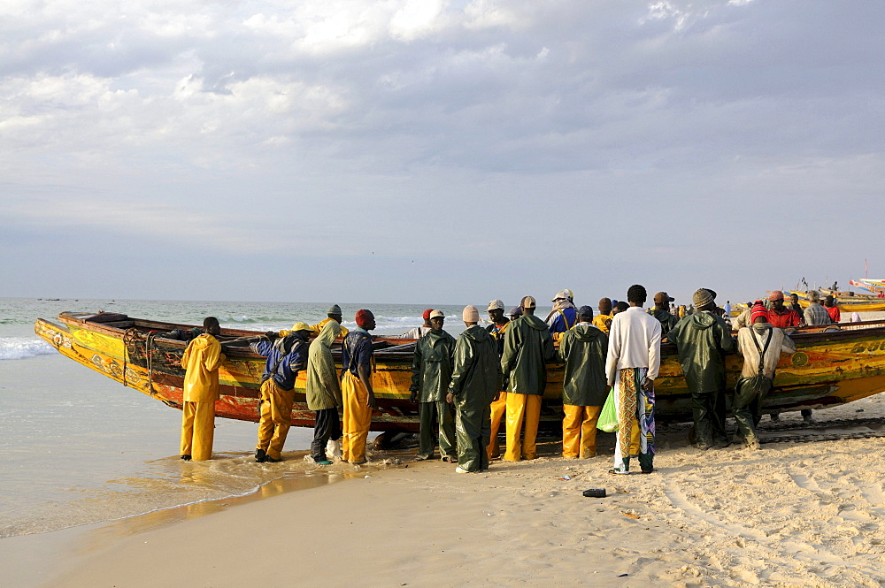 Fishermen pushing their boats back onto the beach, Nouakchott, Western Africa, Mauritania, Africa