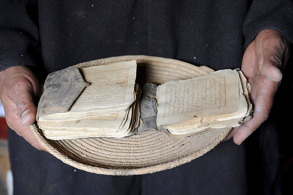 Hands holding old manuscripts of the holy Koran, Ouadane, Mauritania, northwestern Africa