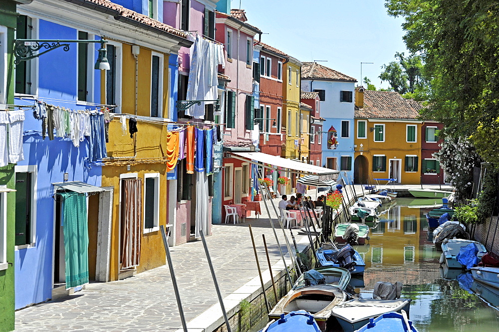 Canal with fishing boats in Burano, a village pub with tourists, fishermen's houses, Burano Island, Venice Lagoon, Venice, Italy, Europe