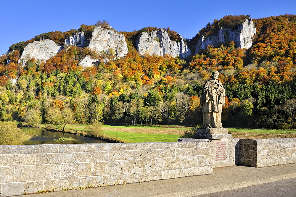 Hausener Bogenbruecke arch bridge with the statue of St. Nepomuk, patron saint of bridges, in front of the peaks of the Hausener Zinnen amidst autumnal vegetation, Sigmaringen district, Baden-Wuerttemberg, Germany, Europe