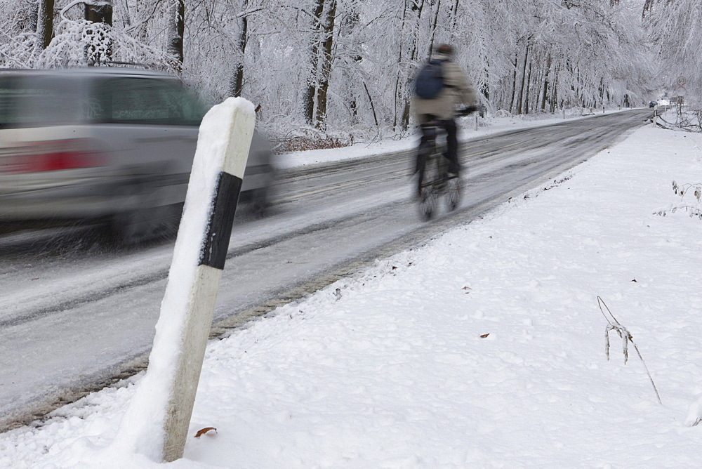 Cyclist being overtaken on a snowy country road in winter, Hesse, Germany, Europe