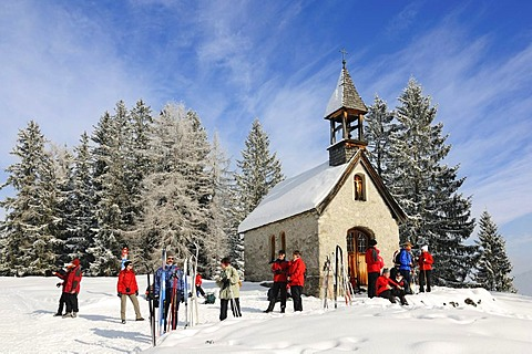 Hikers at St. Anne's Chapel on Germany's first premium winter hiking track, Hemmersuppenalm, Reit im Winkl, Bavaria, Germany, Europe