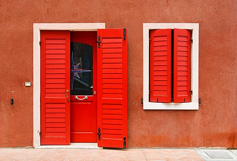 Bright red facade of house, historic town centre of Caorle, Veneto, Italy, Europe