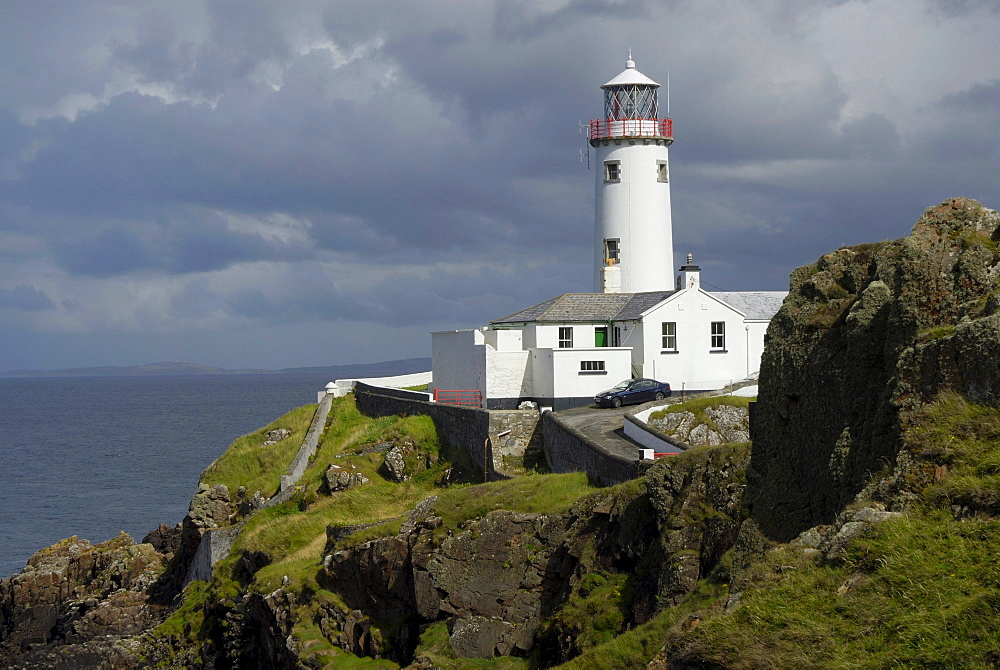 Fanad Head Lighthouse on rocky cliff, rain shower, County Donegal, Ireland, Europe