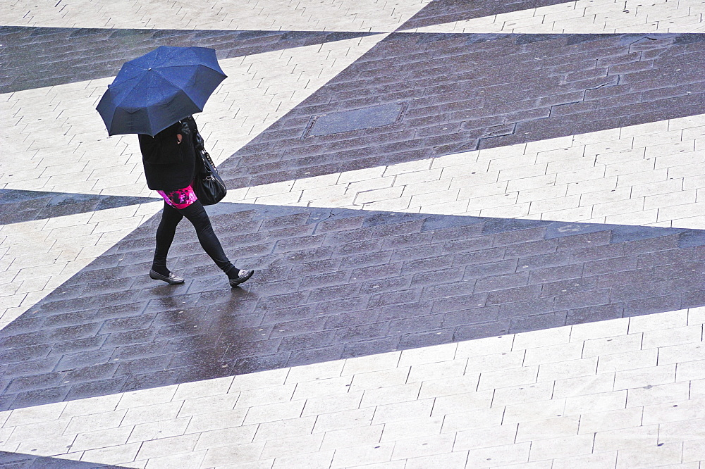 Woman with umbrella at Sergels Torg in the center of Stockholm, Sweden, Europe