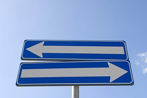 Road sign with two one way signs indicating opposite directions