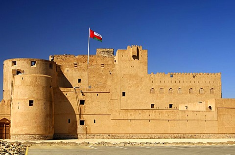 Fort Jabrin flagged with National Flag of Oman, historical clay-made fort in the Dhakiliya Region, Sultanate of Oman, Middle East