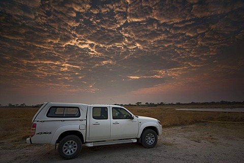 Four-wheel-drive vehicle at sunrise, Hwange National Park, Zimbabwe, Africa