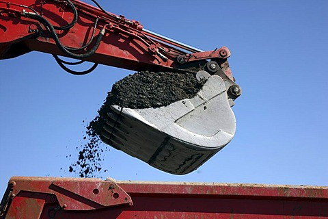 Excavator shovel, laden with soil, construction site