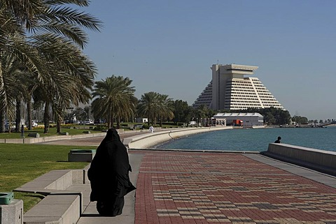 Arabian woman wearing traditional black clothing going for a walk along the Corniche in front of the Sheraton Hotel, West Bay District, Doha, Qatar, Middle East