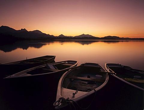 Rowing boats on Hopfensee lake after sunset, Ostallgaeu district, Bavaria, Germany, Europe