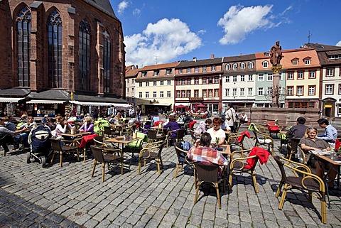 Tourists enjoying the sunshine in the old market square with the Herkulesbrunnen, Hercules Fountain, Heiliggeistkirche, Church of the Holy Spirit, at left, Heidelberg, Rhine-Neckar region, Baden-Wuerttemberg, Germany, Europe