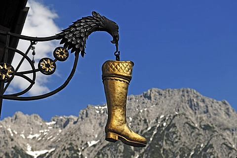 Hanging boot with eagle as an advertising sign of a shoe store, int he back the Karwendelgebirge mountains, Hochstrasse 8, Mittenwald, Upper Bavaria, Bavaria, Germany, Europe