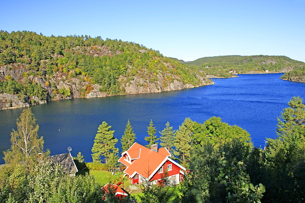 Red wooden house on a fjord near Risor, Scandinavia, Norway, Europe