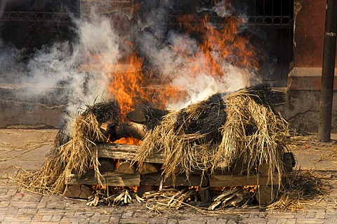Burning pyres with visible body in a traditional funeral, Pashupatinath, Nepal, Asia