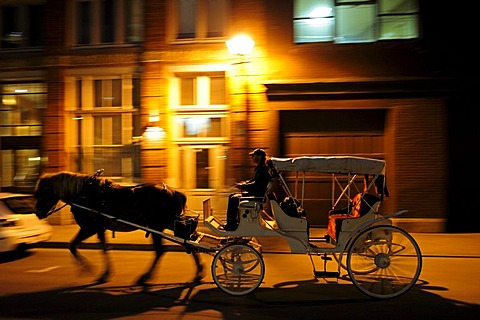 Horse-drawn carriage for tourists driving at night through the streets of the historic old town of Montreal, Quebec, Canada