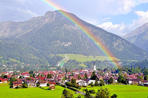 View over Oberstdorf with a rainbow in front of Schattenberg Mountain with the Schattenberg ski-jump, Oberallgaeu, Bavaria, Germany, Europe