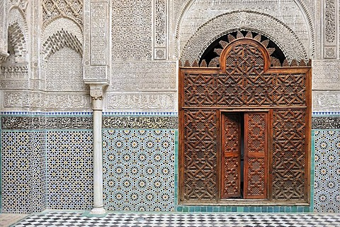 Medersa Attarine, door carved from cedar wood, walls with columns, stucco ornaments and mosaics, Fes, Morocco, Africa