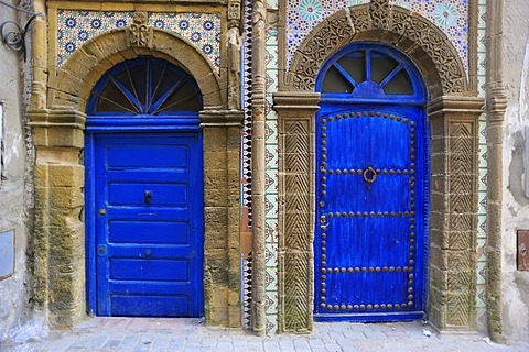 Blue doors of a house, doors surrounded by stone carvings and tile mosaics, Essaouira, Morocco, Africa