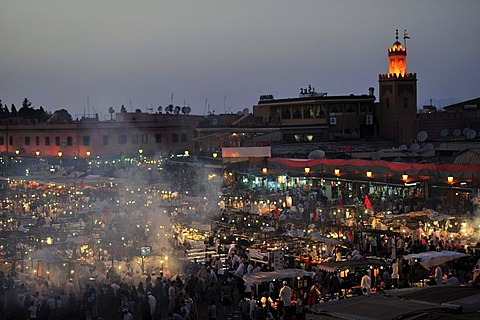 Evening at the Djemaa el Fna market square, literally meaning Assembly of the Dead, with smoke from the many food stalls, behind, the minaret of a mosque, Marrakech, Morocco, Africa