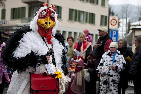 Guggenmusig Familien-Kracher group dressed to the theme of chickens during the carnival procession in Malters, Lucerne, Switzerland, Europe