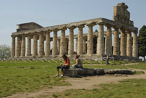 Two girls in front of Temple of Ceres in Paestum, Italy, Europe