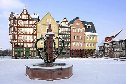 Historic row of houses on market square, market well, snow, winter in Hessenpark, Neu-Anspach, Taunus, Hesse, Germany, Europe