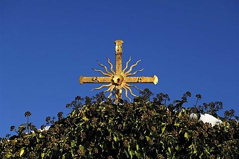 Gilt cross against a blue sky, underneath it ivy (Hedera helix), Goessweinstein, Upper Franconia, Bavaria, Germany, Europe
