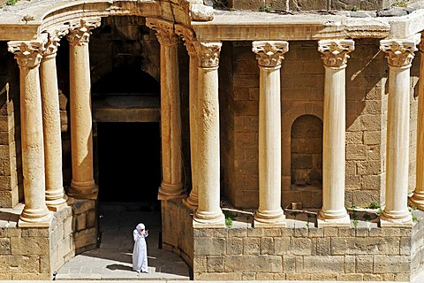 Woman in front of columns, Roman theater in Bosra, Syria, Asia