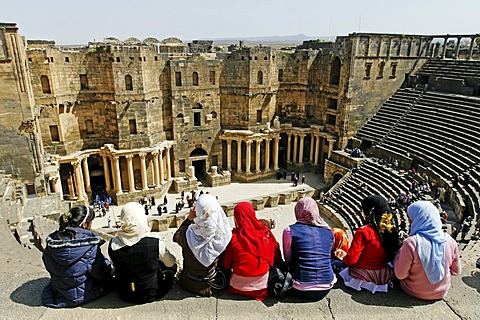 Girls with headscarves sitting on the stairs in the auditorium, Roman theater in Bosra, Syria, Asia