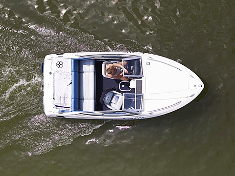 Young man steering a motor boat, from above