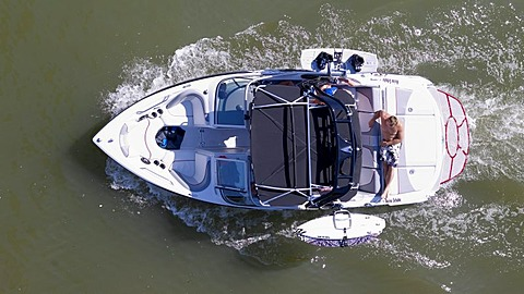 Man taking a sunbath on the deck of a moving sports boat, equipped with wakeboards, from above