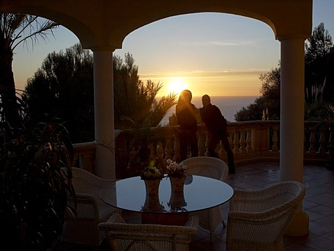 Two women watching the sunset from the terrace of a high quality, stylish apartment, Majorca, Balearic Islands, Spain, Europe