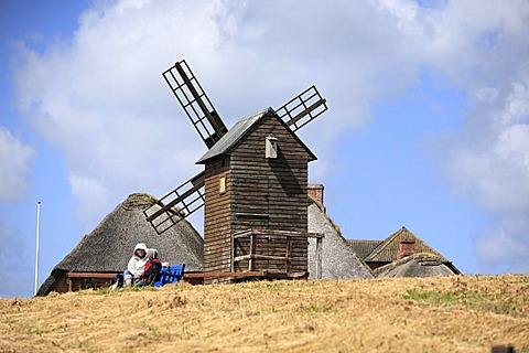 Woman and child sitting under old wooden corn mill from 1926 on the Halligen island of Langeness, Schleswig-Holstein, Germany, Europe