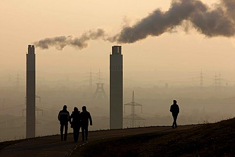 People walking across Hoheward waste dump, in front of chimneys of the AGR incinerating plant, Herten, North Rhine-Westphalia, Germany, Europe - 832-16933