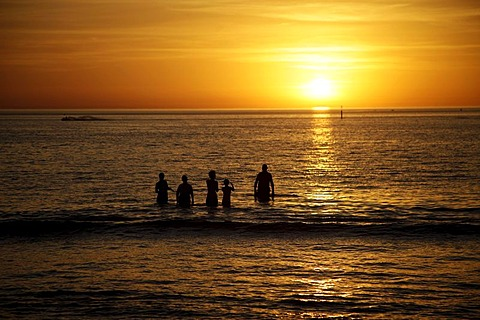 Sunset and swimmers on Glenelg beach, Adelaide, South Australia, Australia